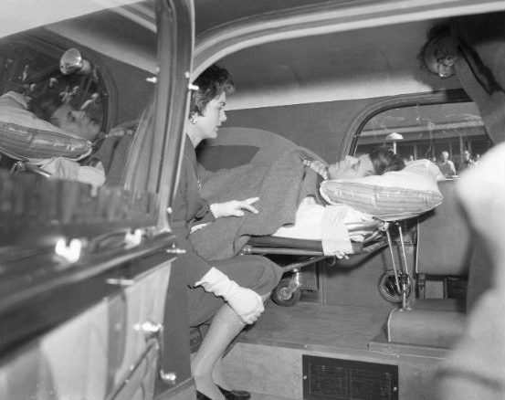 Accompanied by his wife, Jacqueline, Senator John Kennedy is taken by ambulance to his father's residence in West Palm Beach, Florida, for the holidays following surgery in New York. Kennedy underwent the spinal operation to correct a war injury.